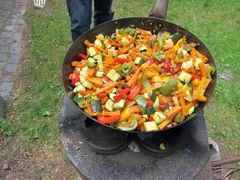 Wok mit Essen auf dem Rocket Stove - Raketengrill