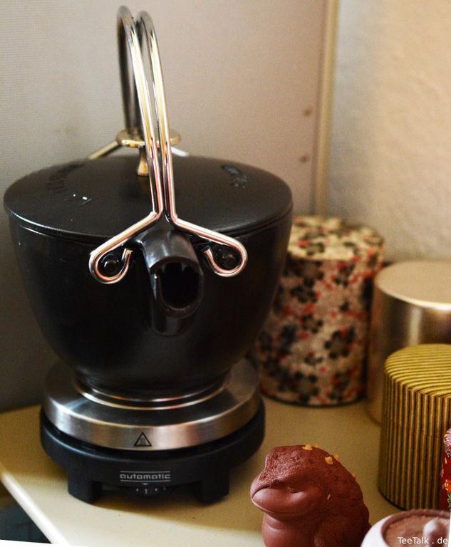 emaillierter Eisenkessel auf Kochplatte, diverse Caddies und ein Teetier